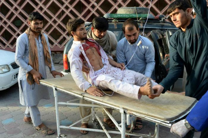 Voluntários levam homem ferido a hospital após ataque. Foto: AFP
