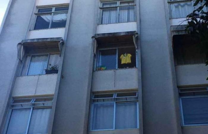 Camisa da Seleção que pertencia a João Lucas pendurada na janela do apartamento onde a criança morava. Foto: Mariana Machado/Esp. CB//D.A PRESS