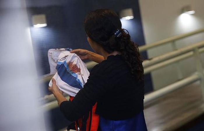Bruna, mãe do adolescente Marcos Vinicius da Silva, segura camisa da escola que o estudante usava Foto: Fernando Frazão/Agência Brasil