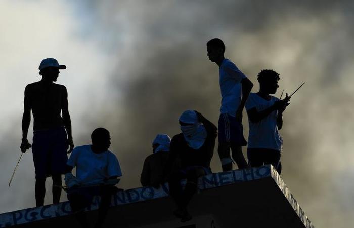 Presos no telhado na prisão de Alcaçuz, região metropolitana de Natal, no início de 2017: parte da insegurança nas ruas tem origem na cadeia (foto: AFP PHOTO / ANDRESSA ANHOLETE)