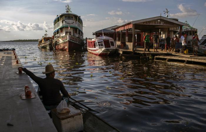 Antenas de televisão, móveis, frutas e todo o tipo de mercadoria são transportados pelas águas do Solimões. Foto: MAURO PIMENTEL / AFP