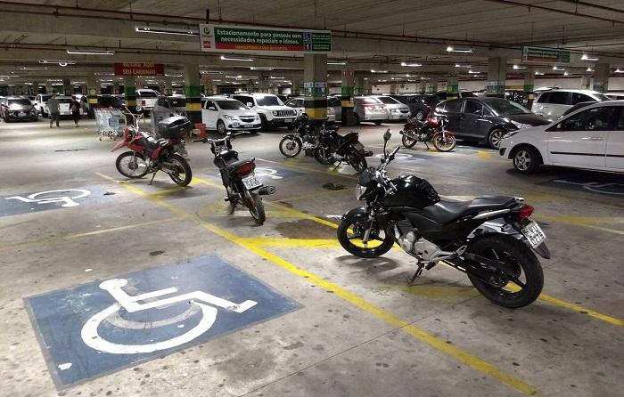 Motos e carro estacionados na área de desembarque das vagas especiais denunciada por um tuite deu início à campanha do supermercado. Foto: Leandro Calça/Divulgação