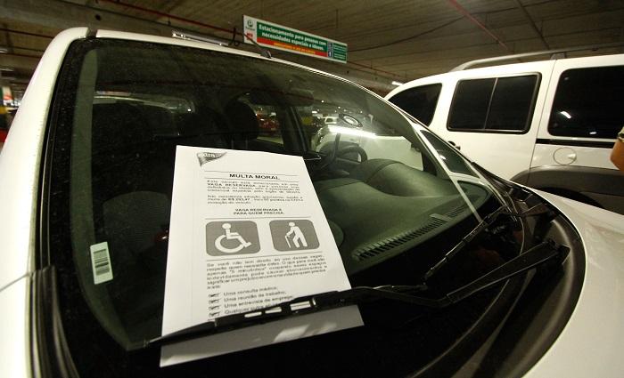 Multa moral é fixada no parabrisa dos carros estacionados de forma irregular nas vagas especiais. Foto: Thalyta Tavares/Esp.DP