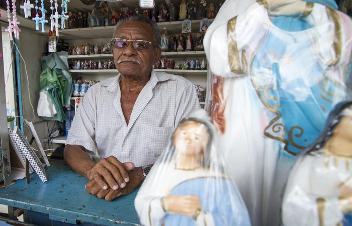 Romildo vende esculturas da santa e itens religiosos ao lado do santuário. Foto: Leo Malafaia/Esp.DP