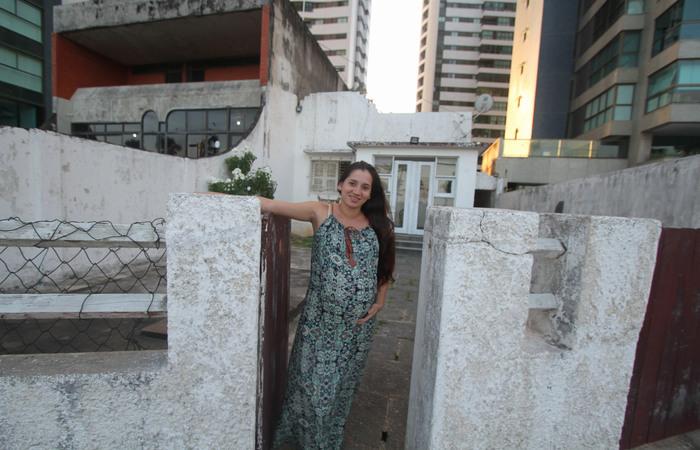 Karine Ane Santos, 22, e sua família vivem no número 52 há três anos, de frente para o mar e cercados por prédios. Foto: Nando Chiappetta/DP