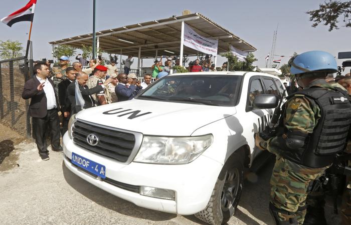 Dois veículos das Nações Unidas atravessaram a barreira, aberta do lado israelense do cruzamento de Quneitra. Foto: LOUAI BESHARA / AFP