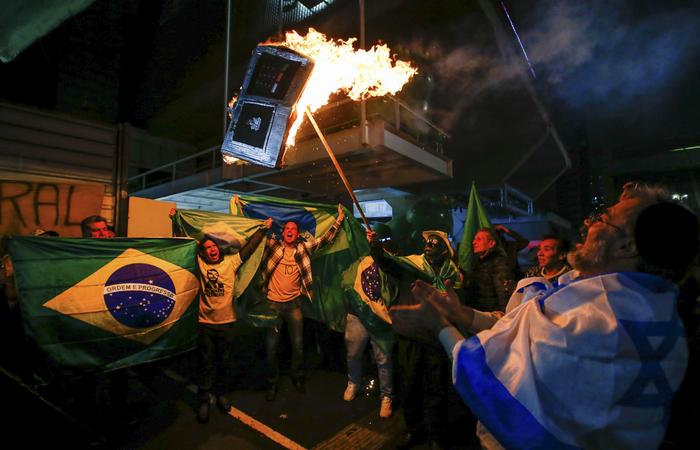 Eleitores de Bolsonaro incendiando urna eletrônica: candidato à presidência questionou diversas vezes a confiabilidade do equipamento. Foto: Alexandre Schneider/AFP