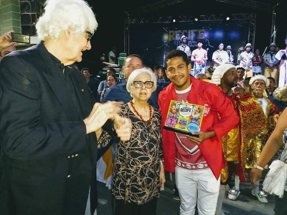 Anderson Santos (presidente do grupo) recebendo o troféu de campeão das mãos da Secretária de Cultura da Prefeitura do Recife, Leda Alves. Foto: Divulgação